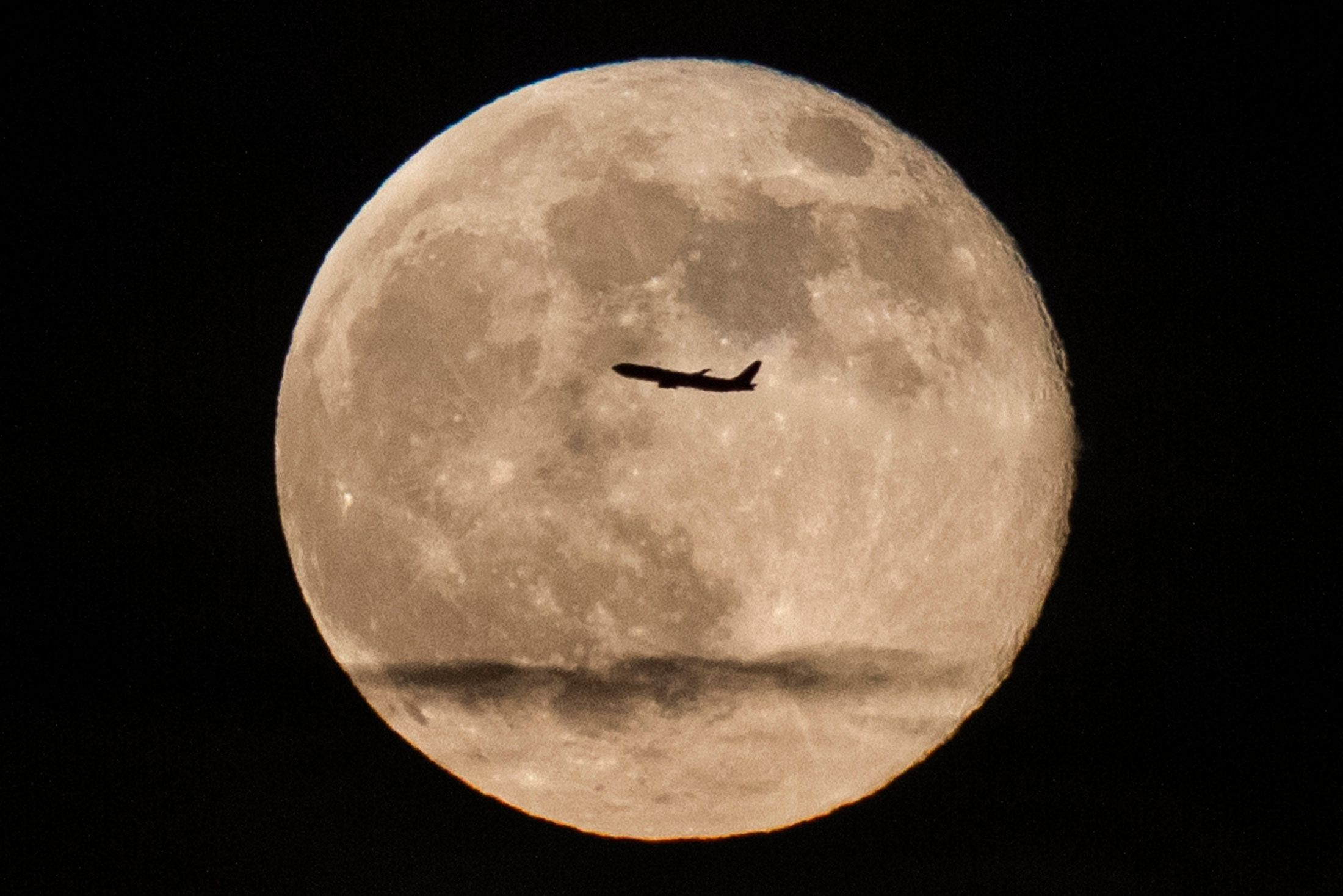 """A silhouetted airplane flies past a 'super moon' over New York on June 23, 2013. The largest full moon of the year called the """"super moon"""" will light up the night sky this weekend.   REUTERS/Zoran Milich (UNITED STATES - Tags: ENVIRONMENT TRANSPORT TPX IMAGES OF THE DAY)"""