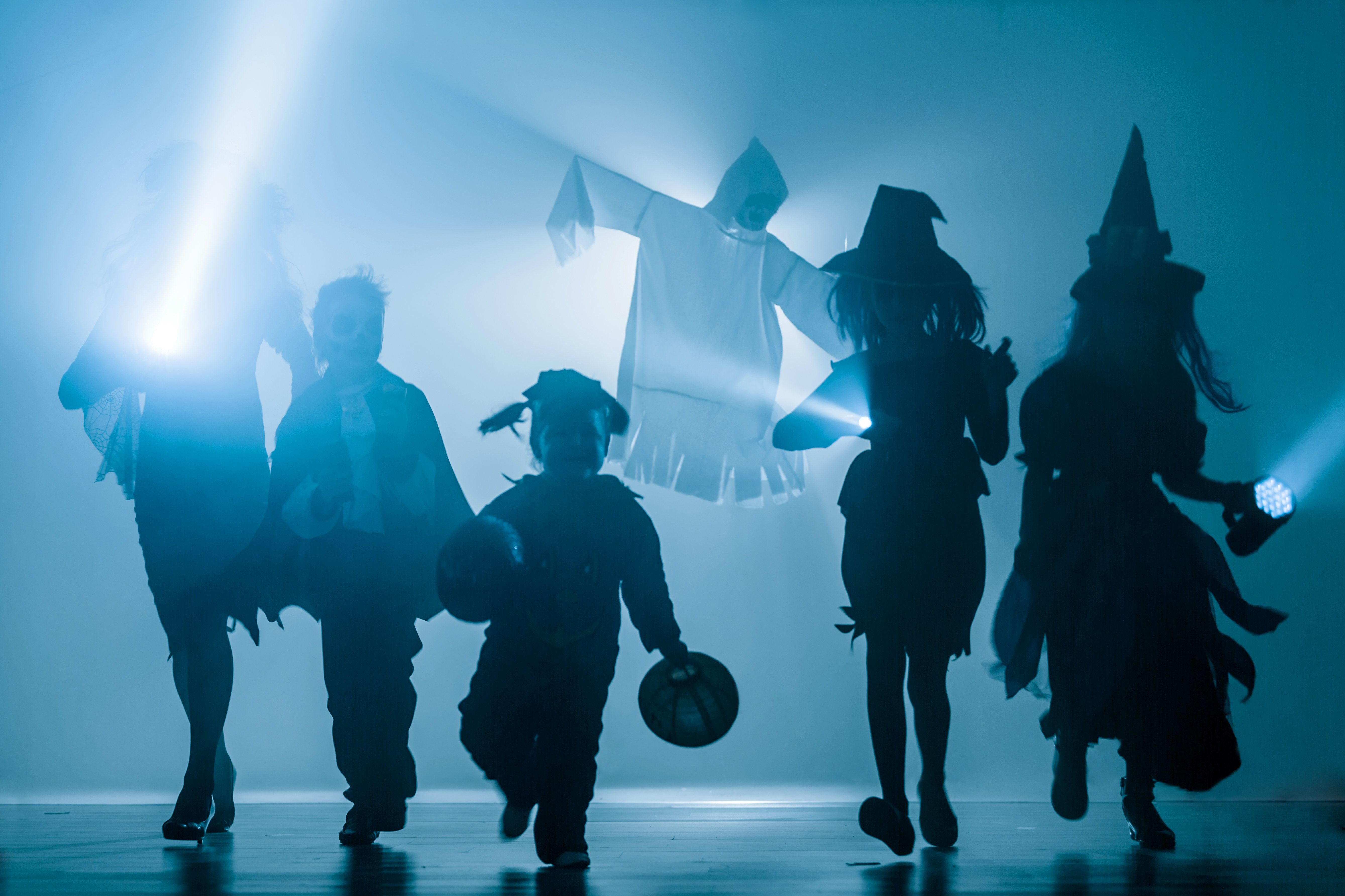 The silhouettes of children dressed in Halloween costumes. Group of children different ages are running directly at the camera. Children are holding flashlights and lanterns in hands. Series of photos. Trick-or-treating and Halloween party. Studio shooting in the dark with backlit in light haze