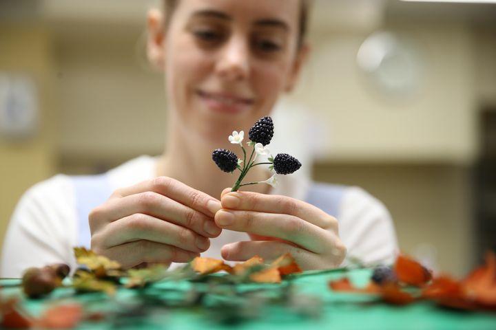 Η ζαχαροπλάστης Sophie Cabot φροντίζει τις τελευταίες λεπτομέρειες του στολισμού με φρούτα και άνθη