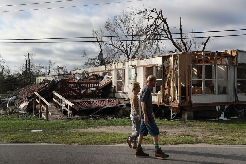 People walk past a home destroyed in Panama City.
