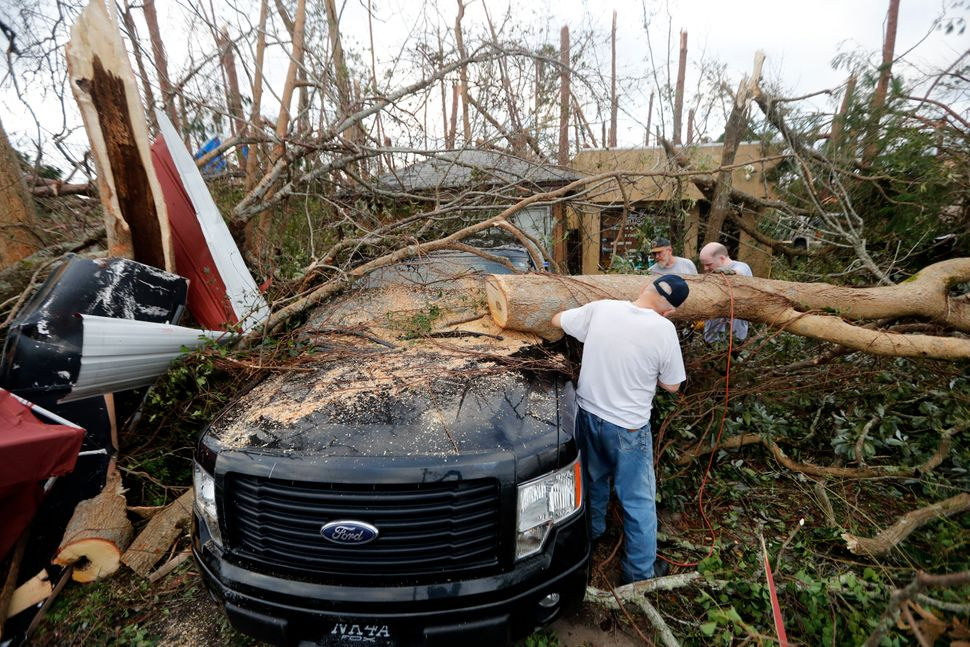 People cut away a tree on a vehicle in Panama City.