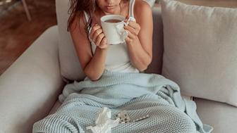 Sick woman laying in bed under blanket and holding cup of tea with medicaments and tissues. Cold medicine and sick woman drinking hot beverage to get well from flu, fever and virus