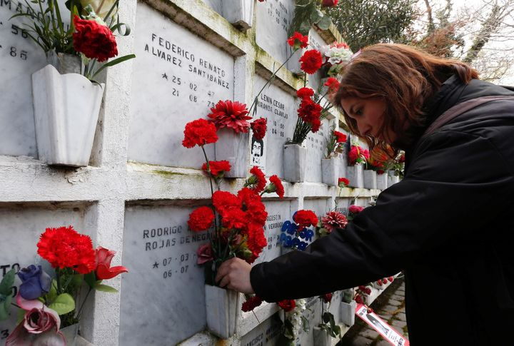 A woman lays flowers at a memorial to victims of Augusto Pinochet's brutal dictatorship in 2017.