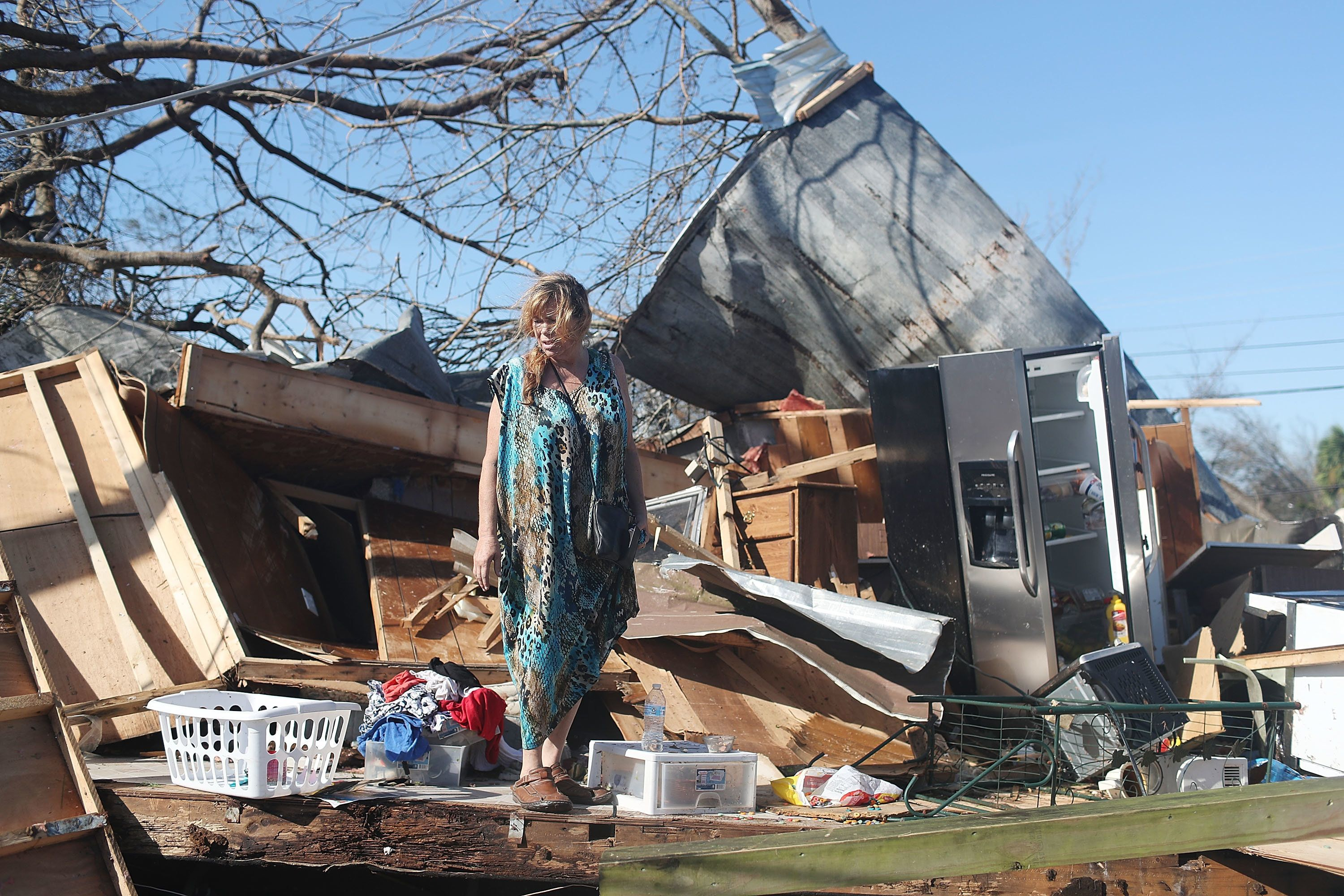 Kathy Coy stands among what is left of her home in Panama City after Hurricane Michael destroyed it. She said she was in the