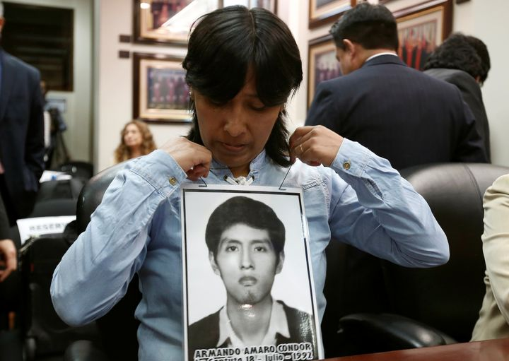 A Peruvian woman with a picture of her brother, a victim of repression during the rule of Alberto Fujimori, before a hearing