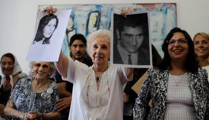 A woman holds pictures of two people who were disappeared while being held as political prisoners during Argentina's mi
