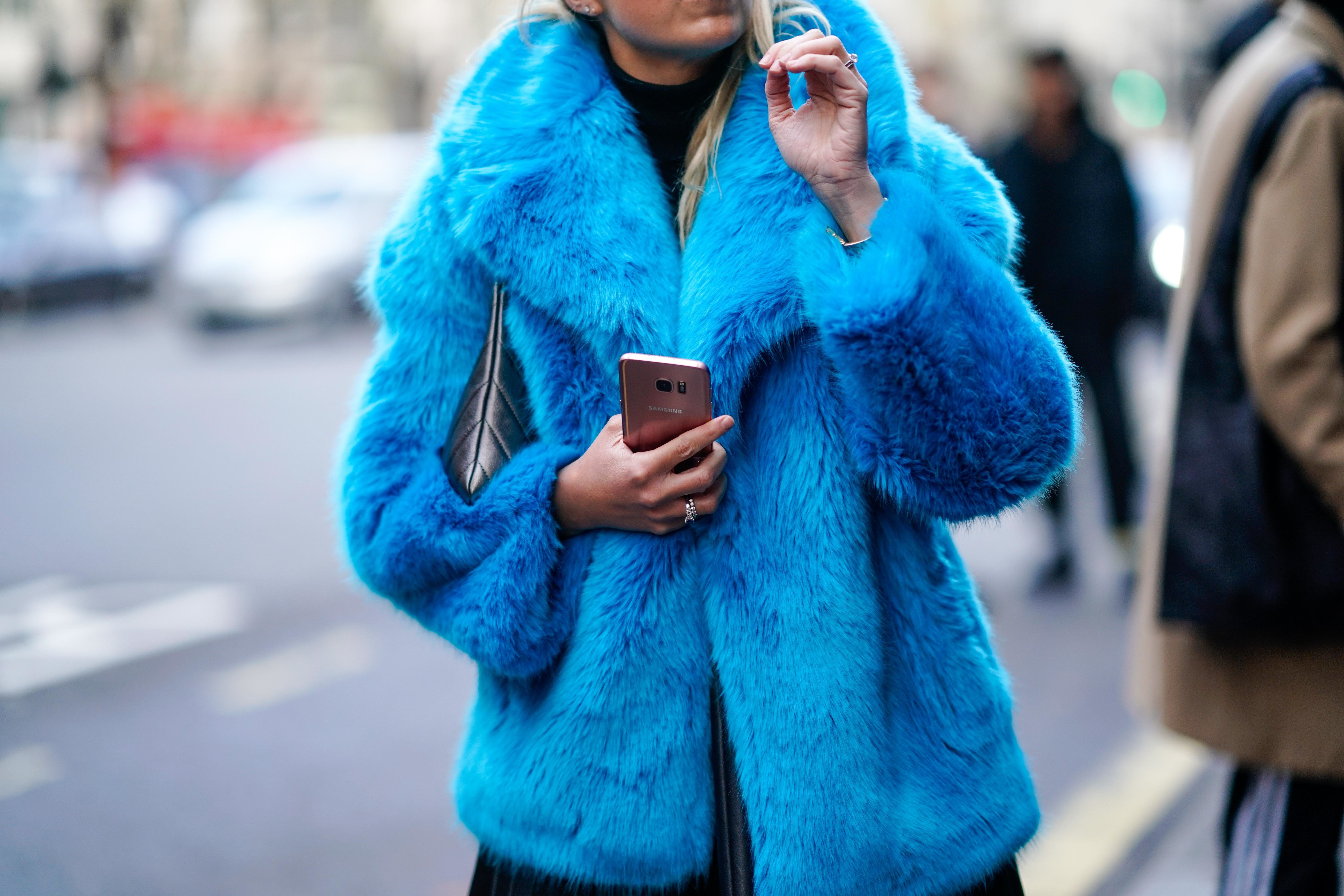 LONDON, ENGLAND - JANUARY 06:  A guest wears a blue faux fur coat, a black pleated skirt, and is holding a smartphone, during London Fashion Week Men's January 2018 at  on January 6, 2018 in London, England.  (Photo by Edward Berthelot/Getty Images)