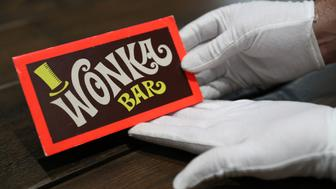 A Prop Store employee holds a Wonka Bar from the film Willy Wonka & the Chocolate Factory (estimate £8-10,000) in the Prop Store head office near Rickmansworth ahead of the Entertainment Memorabilia Live Auction on 20th September.