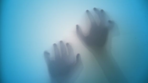 Silhouette of young female creepy hand on frosted glass.