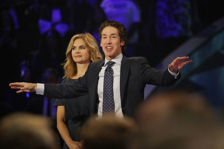 Joel Osteen, the pastor of Lakewood Church, stands with his wife, Victoria Osteen, as he conducts a service at his church on