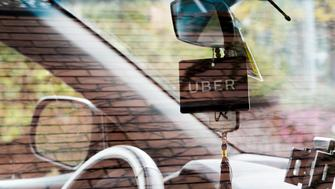 Side view of the window of a Uber car with the black Uber credential (logo) hanging on the rear-view mirror.