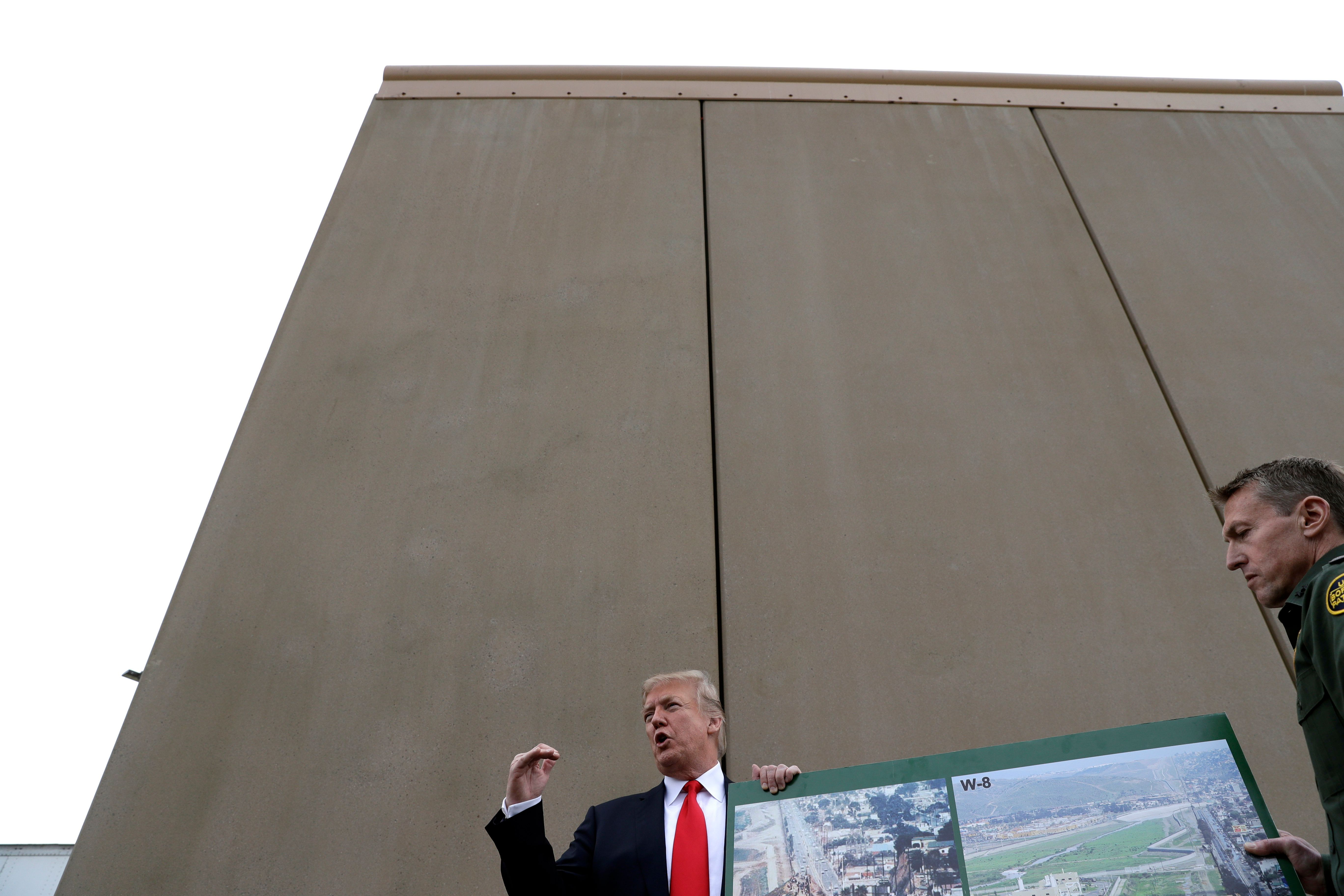 President Donald Trump speaks during a tour as he reviews border wall prototypes, Tuesday, March 13, 2018, in San Diego, as Rodney Scott, the Border Patrol's San Diego sector chief, listens at right. (AP Photo/Evan Vucci)