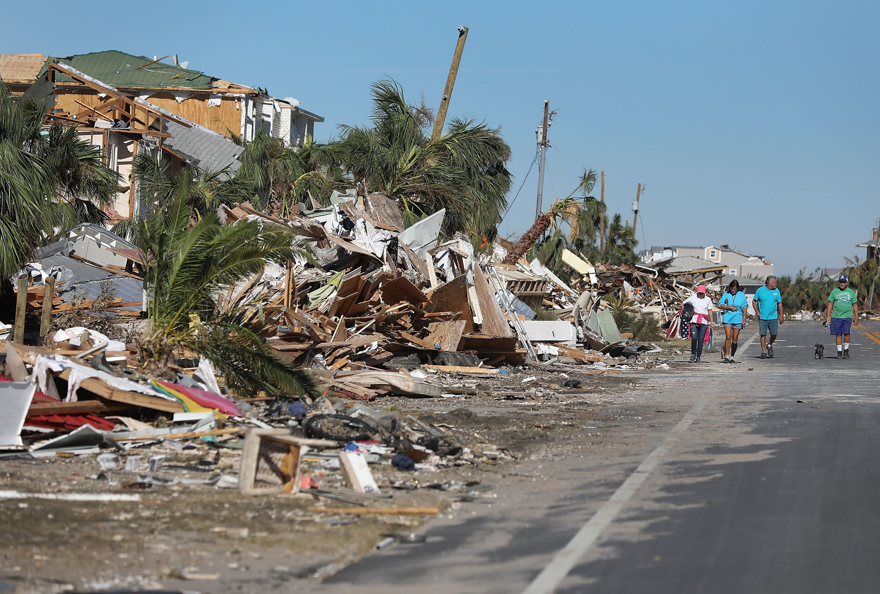 MEXICO BEACH, FL - OCTOBER 12:  People walk along a debris strewn street after Hurricane Michael passed through the area on October 12, 2018 in Mexico Beach, Florida.  The hurricane hit the panhandle area with category 4 winds causing major damage.  (Photo by Joe Raedle/Getty Images)