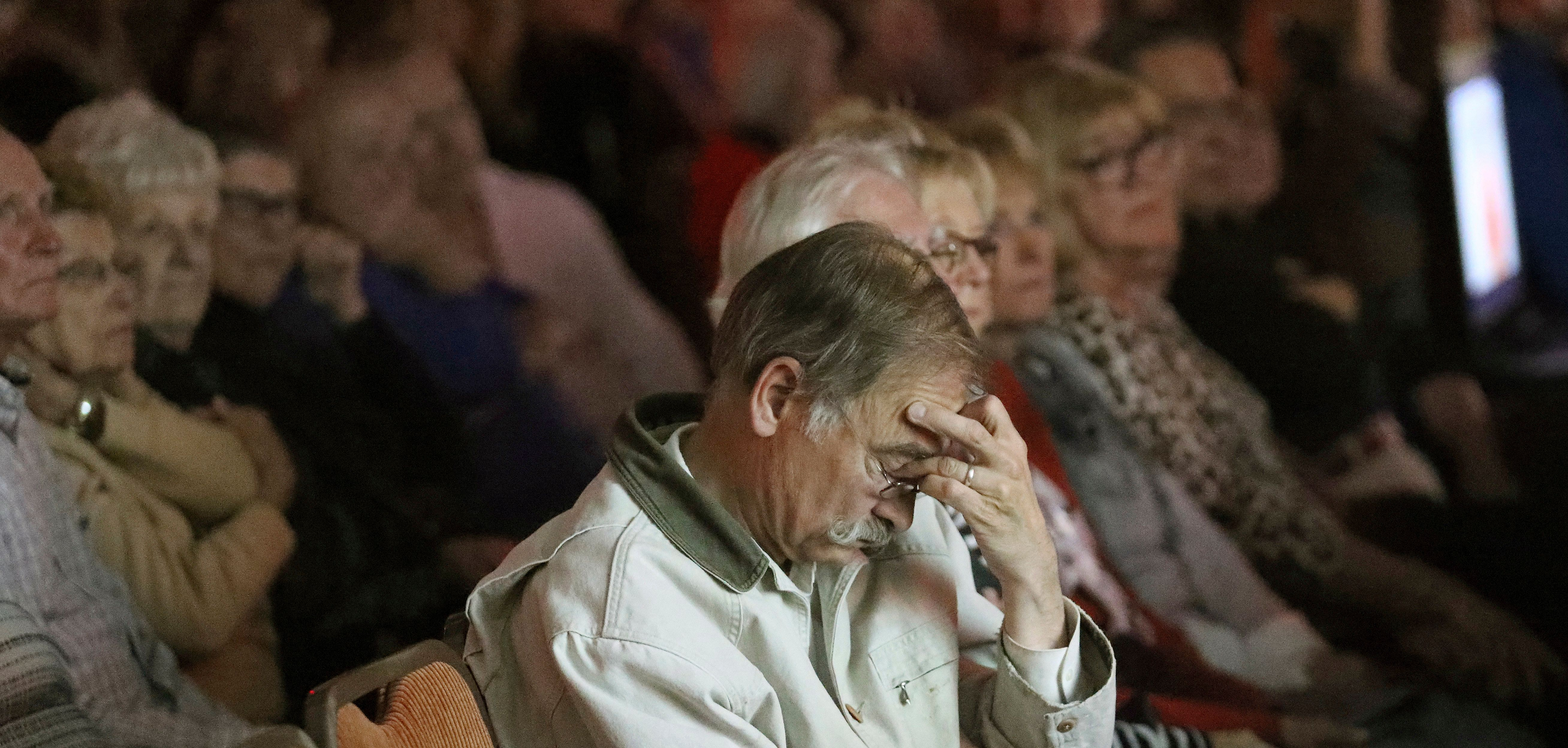 In this Tuesday, Oct. 9, 2018, photo, people watch a taped interview of Russell Henderson, who is currently serving two consecutive life sentences for the murder of Matthew Shepard, during a community forum in Laramie, Wyo. About 200 people attended the forum questioning the prevailing view Shepard was murdered because of his sexual orientation. (AP Photo/Rick Bowmer)