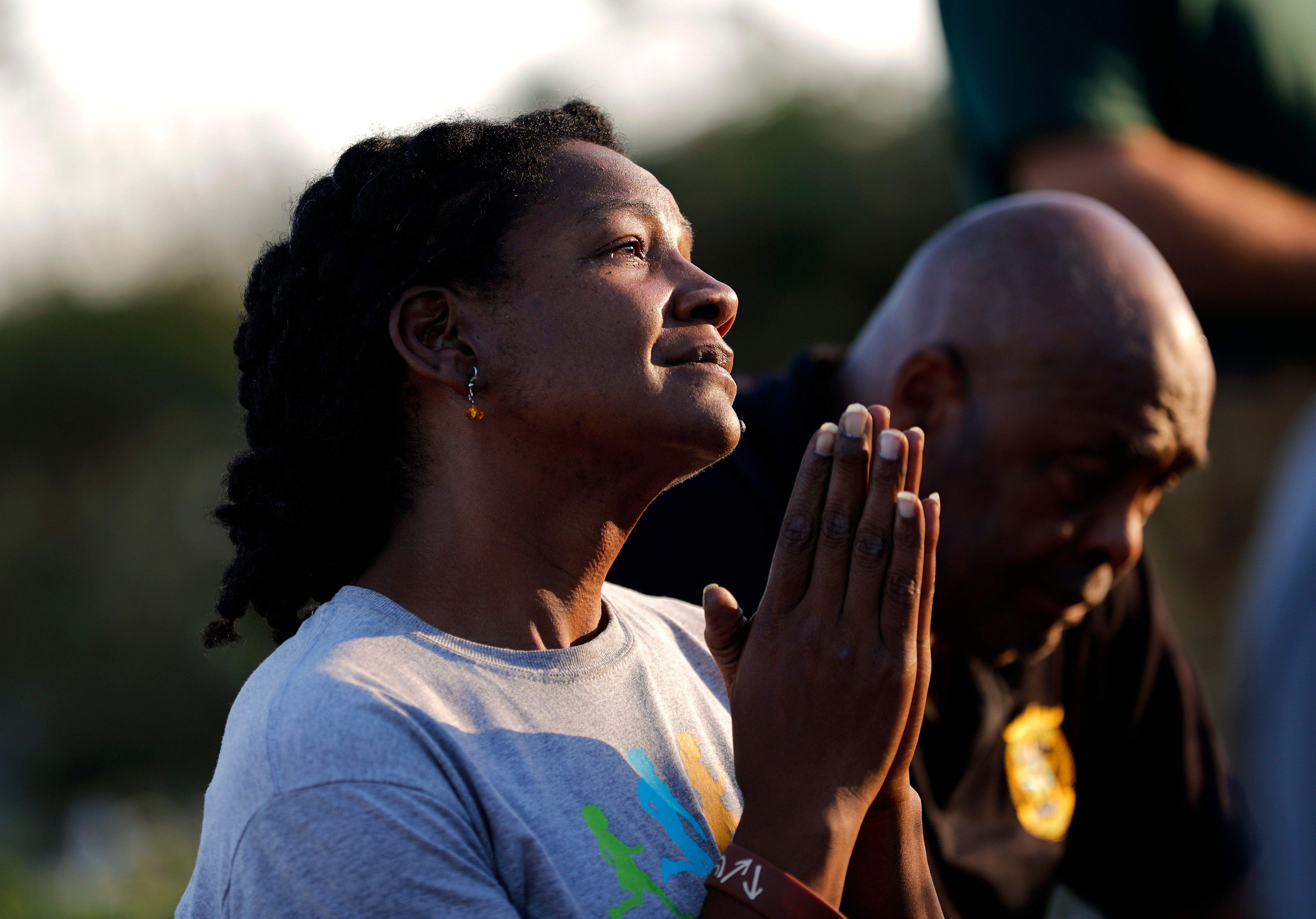 Lora McCalister-Cruel prays during Mass which was moved outdoors due to damage from Hurricane Michael inside Saint Dominic Catholic Church in Panama City, Fla., Saturday, Oct. 13, 2018. (AP Photo/David Goldman)