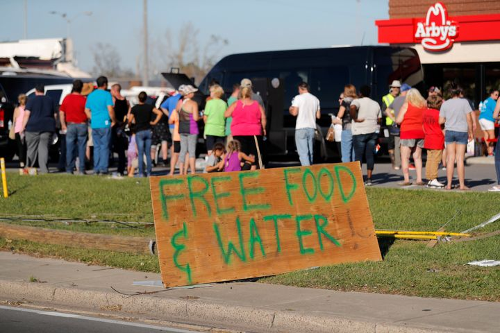 People line up for free food and water in the aftermath of Hurricane Michael in Panama City, Fla., Saturday, Oct. 13, 2018. (