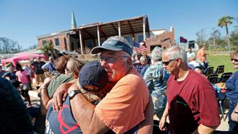 Jerry Register, a congregation member of St. Andrew United Methodist Church, hugs a fellow church member during Sunday service, outside the damaged church in the aftermath of Hurricane Michael in Panama City, Fla., Sunday, Oct. 14, 2018. (AP Photo/Gerald Herbert)