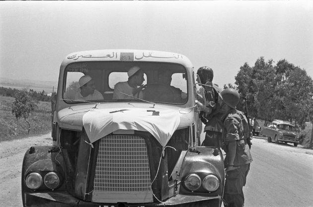 Des parachutistes français s'arrêtent et inspectent une ambulance improvisée devant...