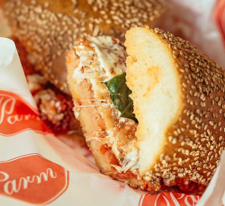 The chicken parm sandwich from Parm is a breaded, enormous hunk of chicken covered in overflowing, melty mozz and red sauce.