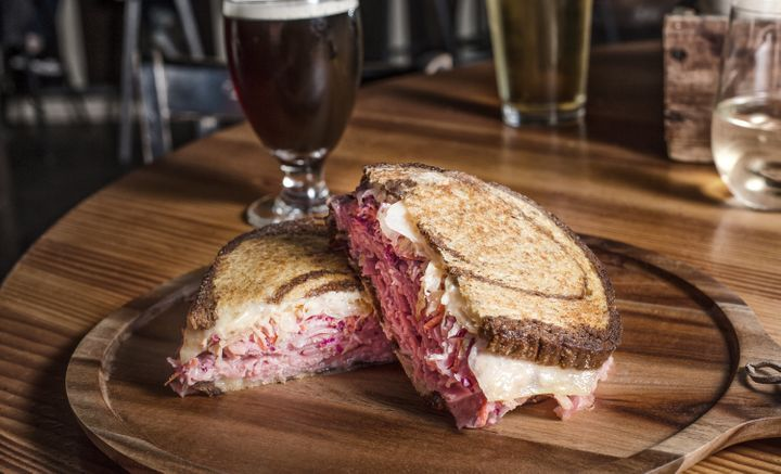 A sandwich that pairs well with beer: corned beef, juniper berry sauerkraut, Swiss and purple slaw slathered with Sriracha Russian dressing and piled onto marble rye.