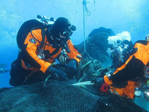 Divers from Ghost Fishing work to recover a massive fishing net abandoned a decade ago off the coast...