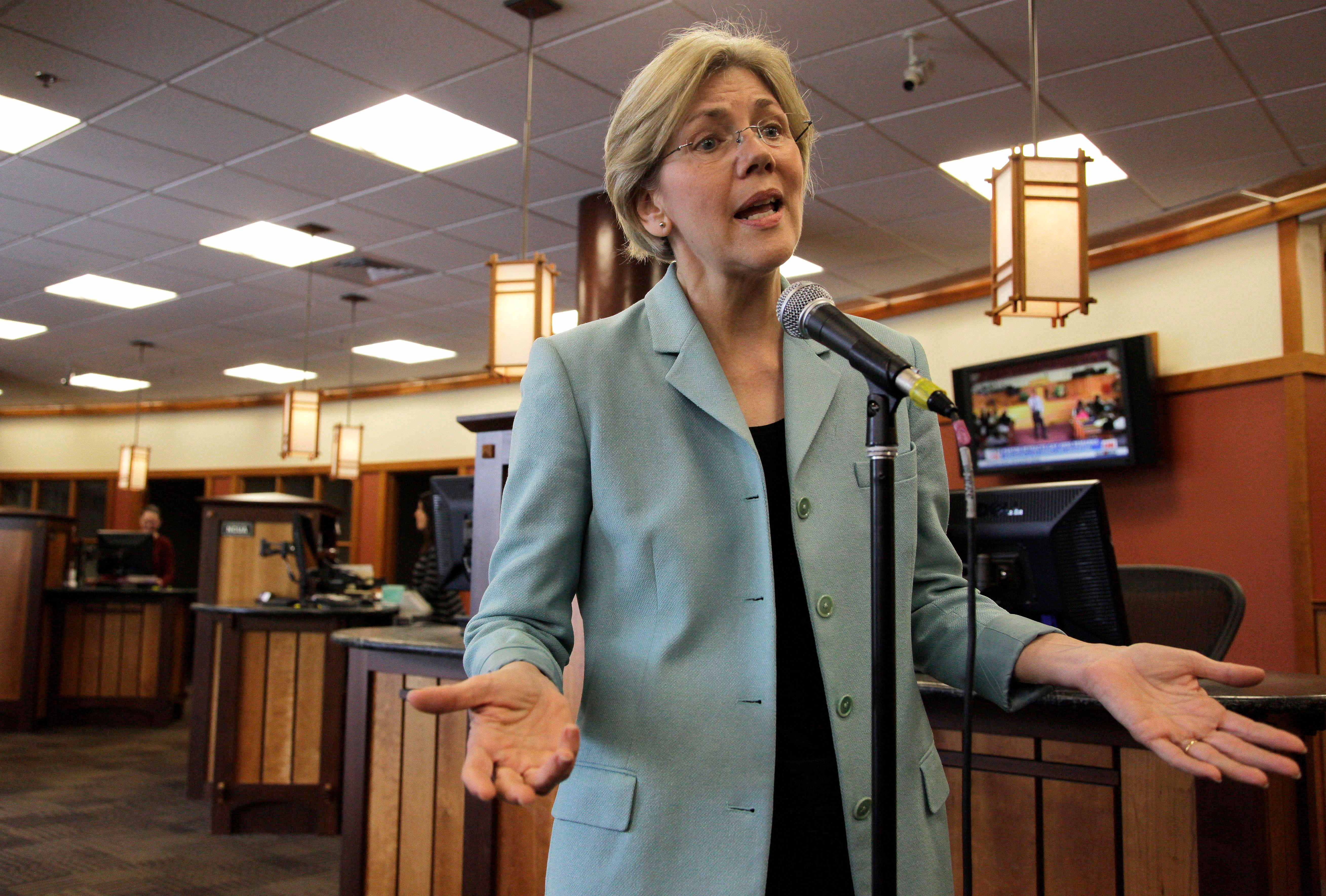 """In this May 2, 2012 photo, Democratic candidate for the U.S. Senate, Elizabeth Warren, speaks to reporters during a news conference while campaigning at Liberty Bay Credit Union headquarters in Braintree, Mass. Warren addressed questions on her claim of Native American heritage. Warren, a Harvard Law School professor who is running in Massachusetts against Republican incumbent Scott Brown, was listed as Native American in several law school directories. Warren has said that her """"family lore"""" described Indian ancestors, and the New England Genealogy Association said it found indications that Warren had a Cherokee great-great-great grandmother, which would make her 1/32 Indian. (AP Photo/Steven Senne)"""