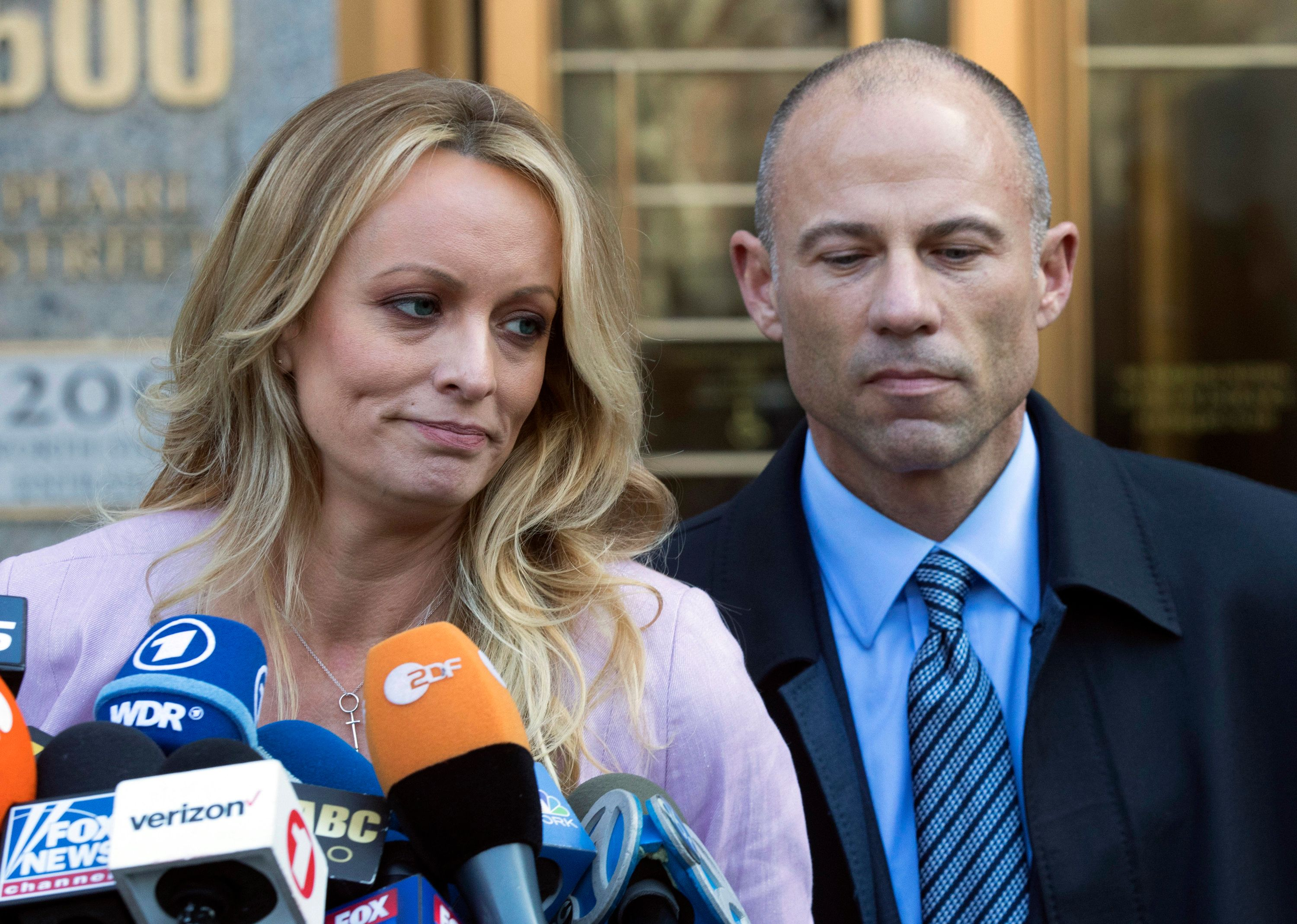 """FILE - In this April 16, 2018 file photo, adult film actress Stormy Daniels, left, stands with her lawyer Michael Avenatti as she speaks outside federal court, in New York. The Justice Department says Avenatti, made """"misrepresentations"""" in a bankruptcy case involving his former law firm that owes more than $440,000 in unpaid federal taxes. Avenatti said Wednesday, July 4, 2018, he doesn't owe any money personally and called the court filing """"politically motivated."""" (AP Photo/Mary Altaffer, File)"""