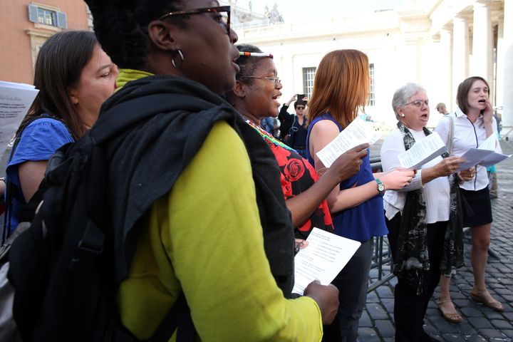 Members of a women's group sing in protest at the Synod Hall before the opening of the Synod of Bishops on 'Young People' on