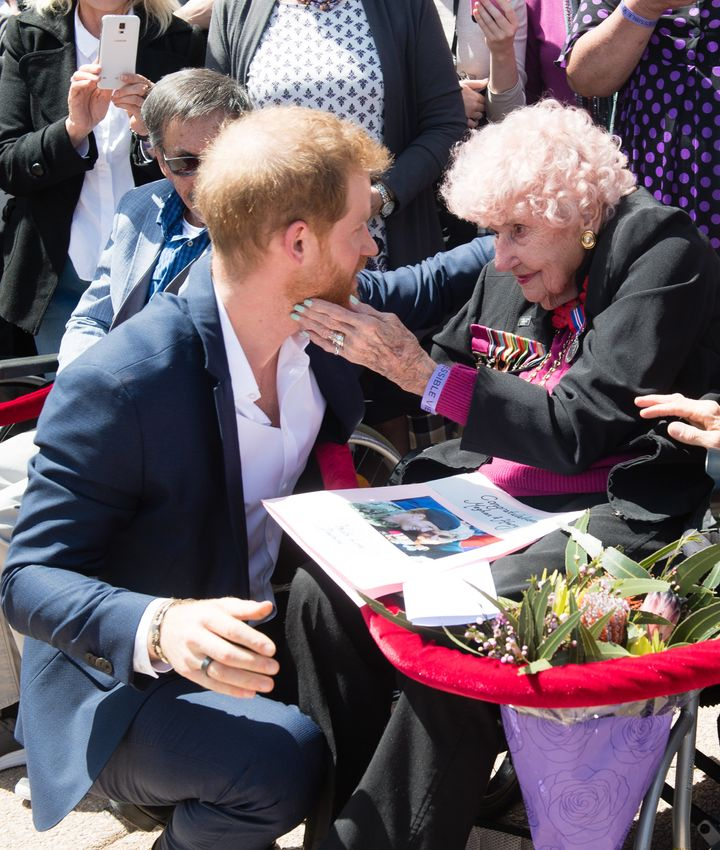 Prince Harry greets royal fan and war widow Daphne Dunne as they arrive for a public walkabout at the Sydney Opera House on Oct. 16, in Sydney, Australia.