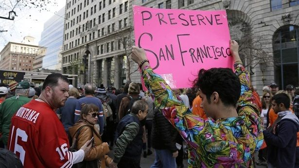 Shane Zaldivar holds up a sign as crowds jam a Super Bowl event in San Francisco. Zaldivar said the sign was a protest agains