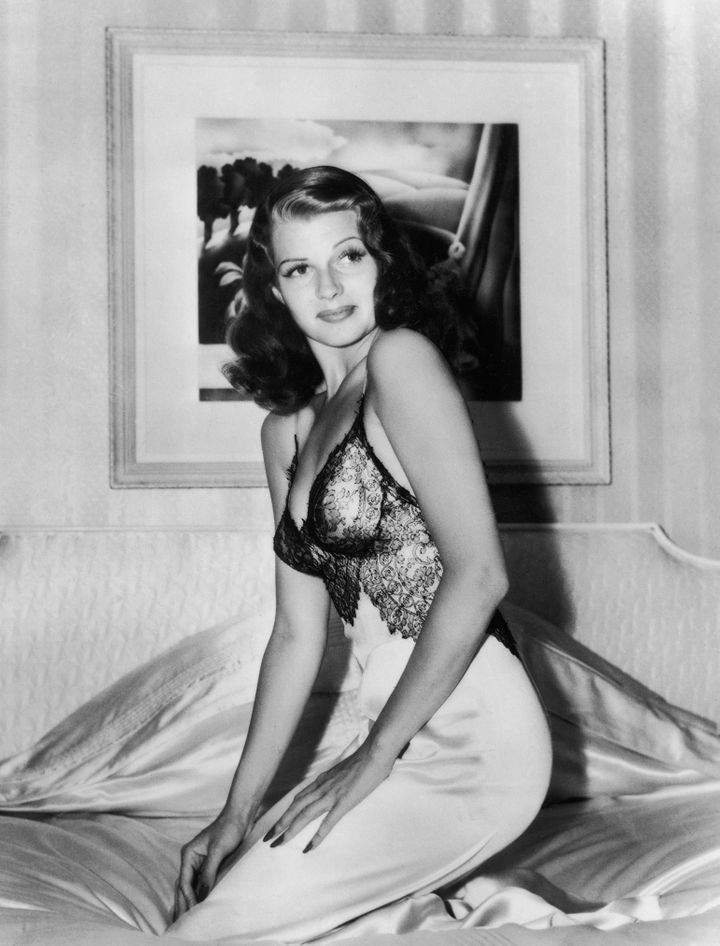 Hayworth in a sheer-topped black and white nightgown kneeling on the satin sheets of her bed at home.