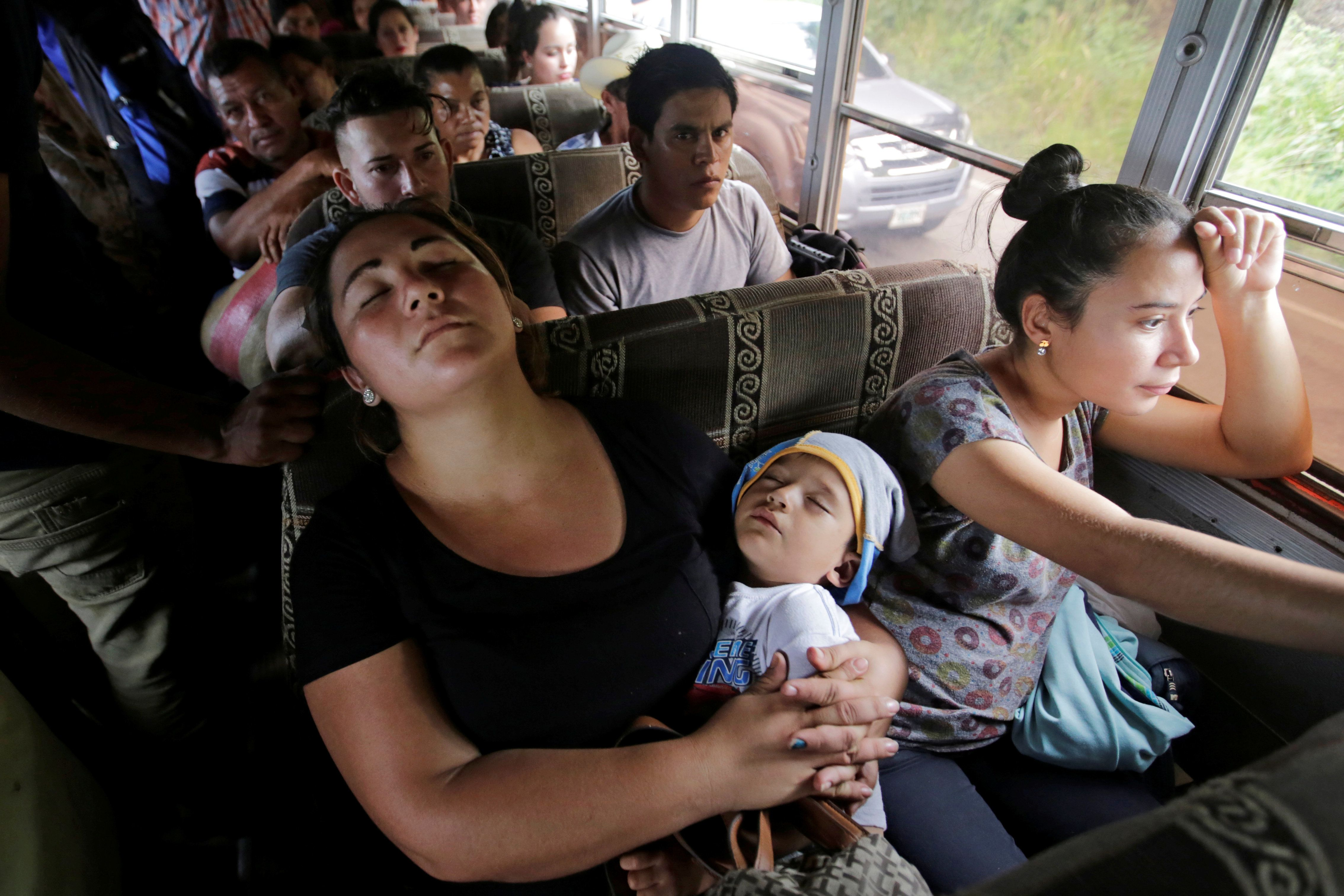 <p>A woman sleeps with her baby as they travel with fellow Hondurans fleeing poverty and violence on a bus in a caravan toward the United States, in the west side of Honduras, Oct. 14, 2018. (Photo: Jorge Cabrera/Reuters) </p>