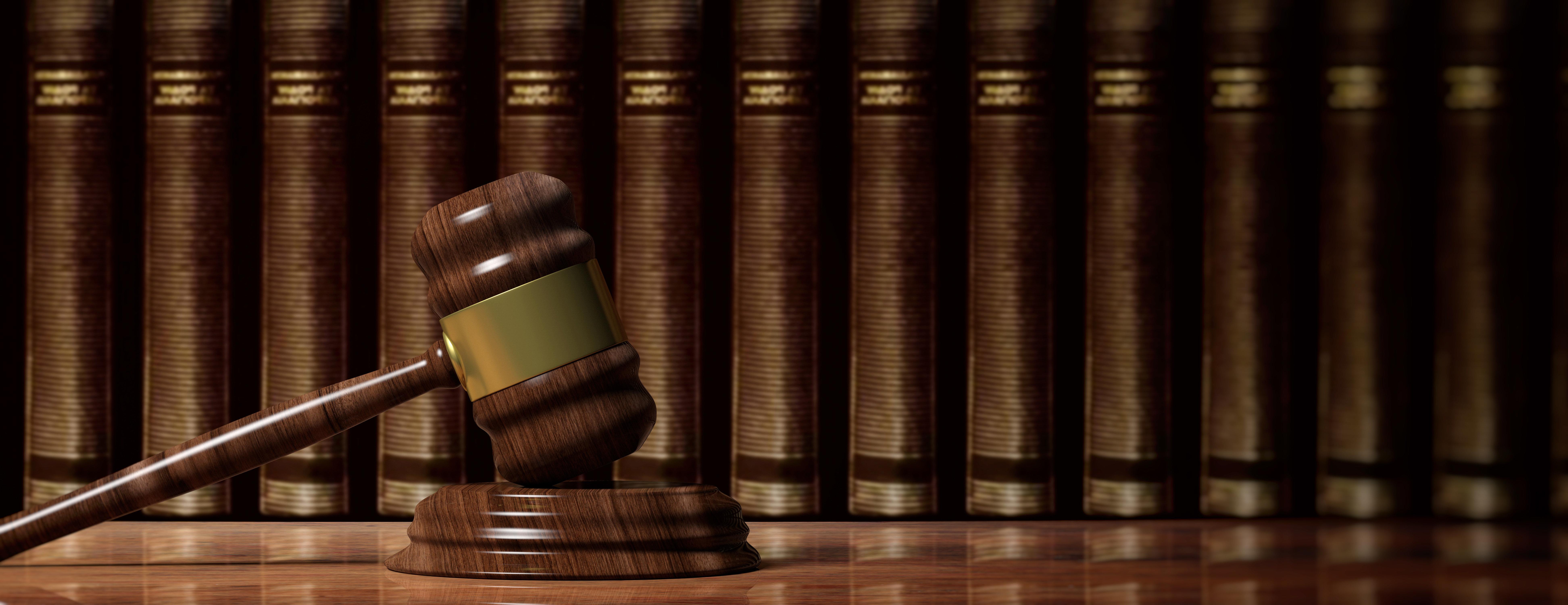 Law concept. Wooden judge gavel on law books background, banner. 3d illustration