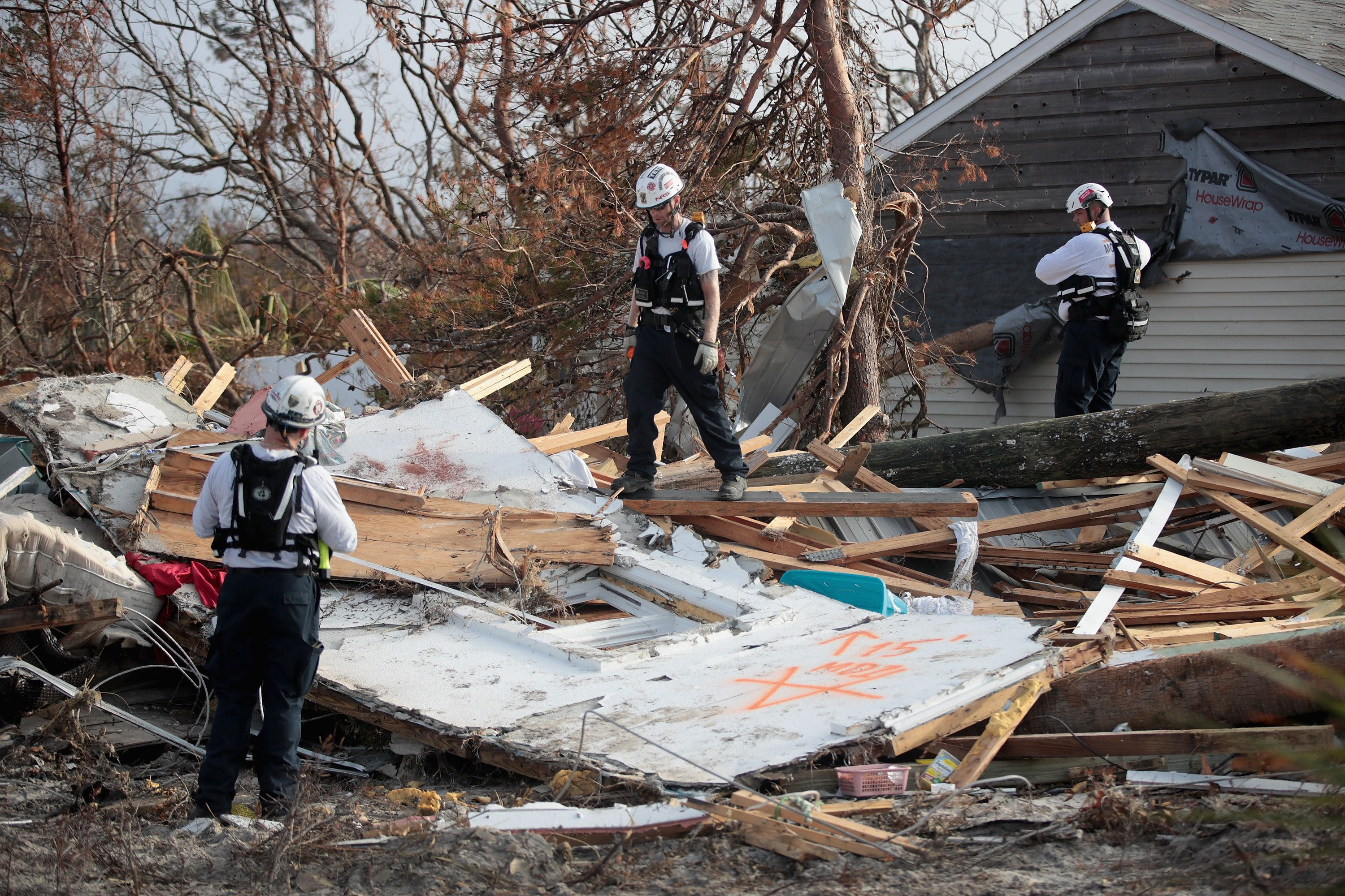 MEXICO BEACH, FL - OCTOBER 16: Members of the Maryland Task Force urban search and rescue team mark a location for a detailed search after getting a reaction from their cadaver dog indicating a possible victim of Hurricane Michael on October 16, 2018 in Mexico Beach, Florida. Hurricane Michael slammed into the Florida Panhandle on October 10, as a category 4 storm, claiming at least 19 lives and causing massive damage.  (Photo by Scott Olson/Getty Images)