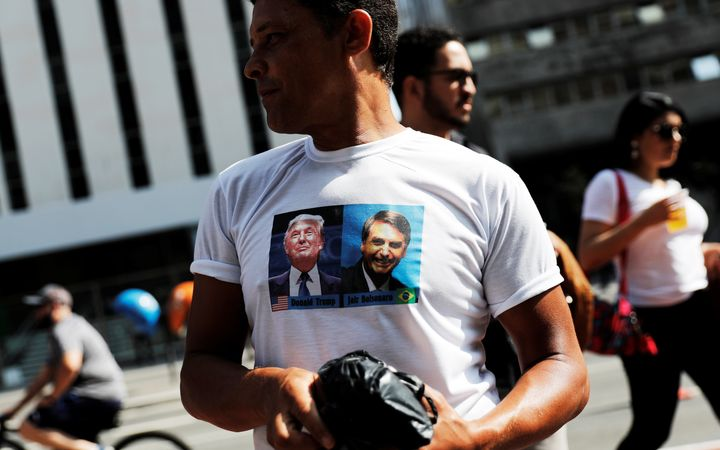 A supporter of Brazilian presidential front-runner Jair Bolsonaro wears a T-shirt twinning with the candidate's image with th