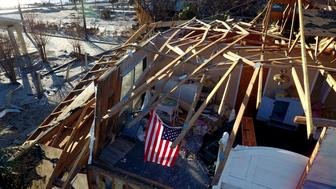 An American flag hangs in a bedroom of a damaged home from Hurricane Michael in Mexico Beach, Fla., Tuesday, Oct. 16, 2018. (AP Photo/David Goldman)