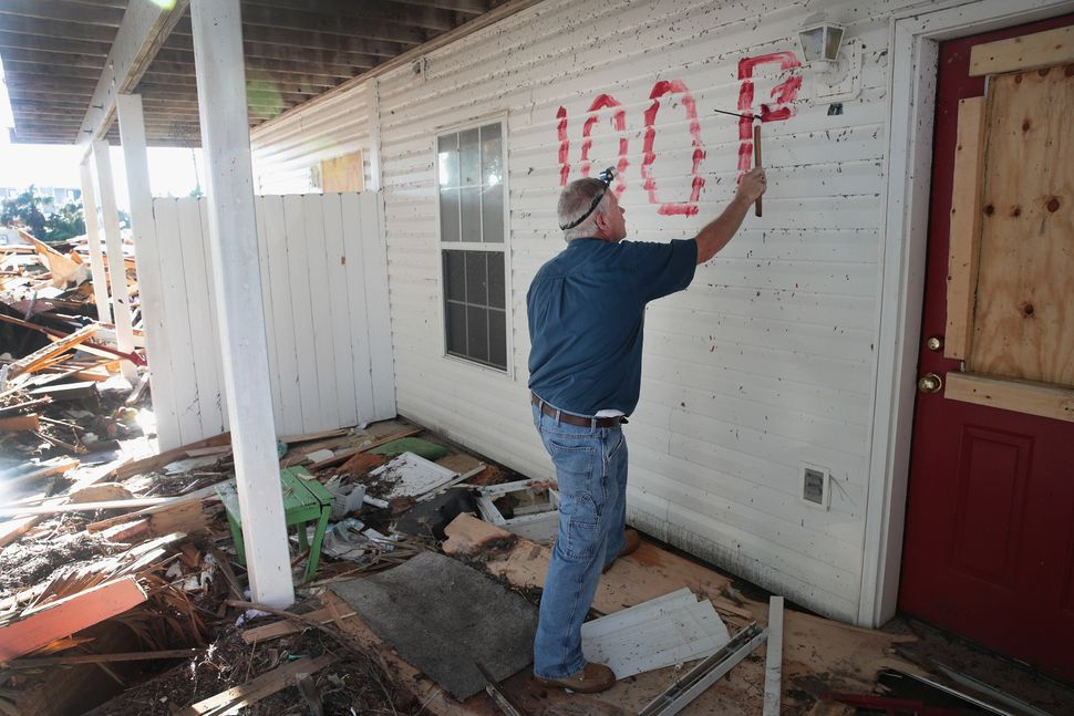 Denney Pate paints an address on a home to make it easier for the insurance adjuster and contractors to locate it after sever