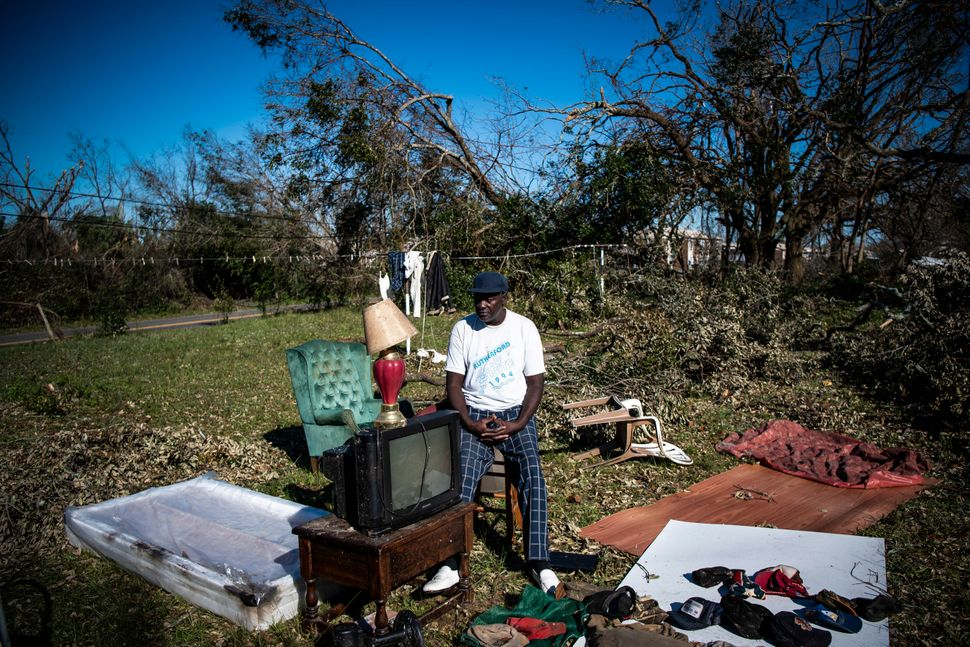 Bobby Lee Cooper, 63, sits out in his yard trying to dry items from his home in Springfield, Florida. Cooper lives in a small