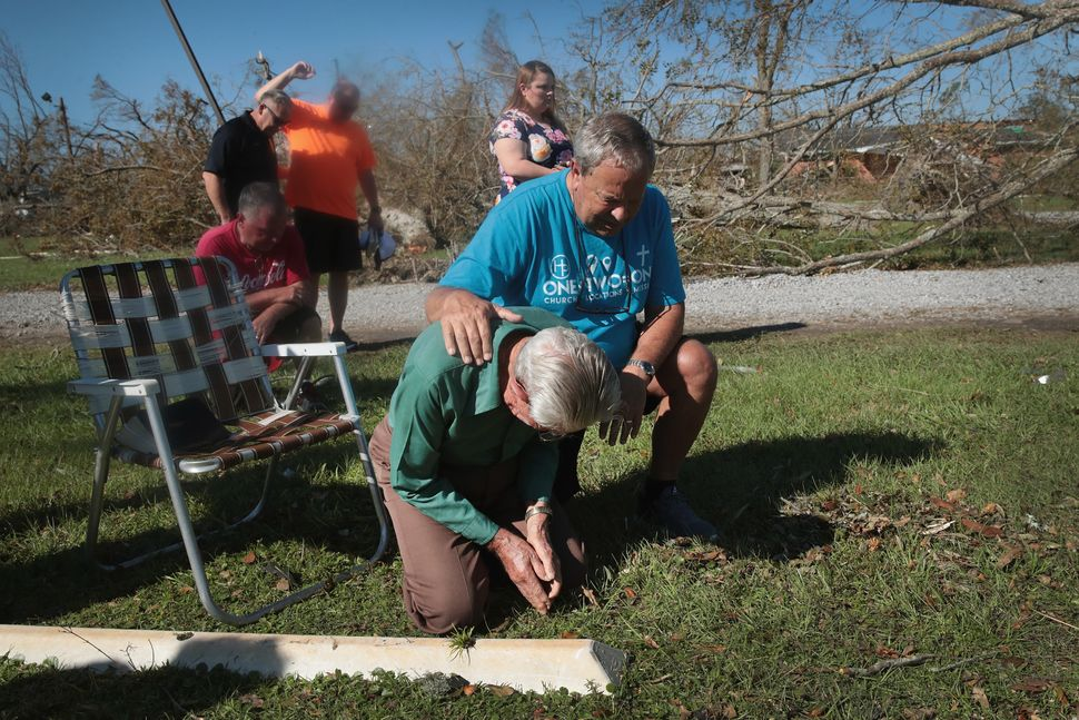 Worshipers at Hiland Park Baptist Church attend Sunday service in the parking area of the church in Panama City.