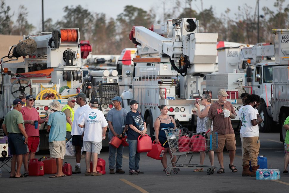 Victims of Hurricane Michael wait in line to receive a donation of up to five gallons of gas in Panama City.