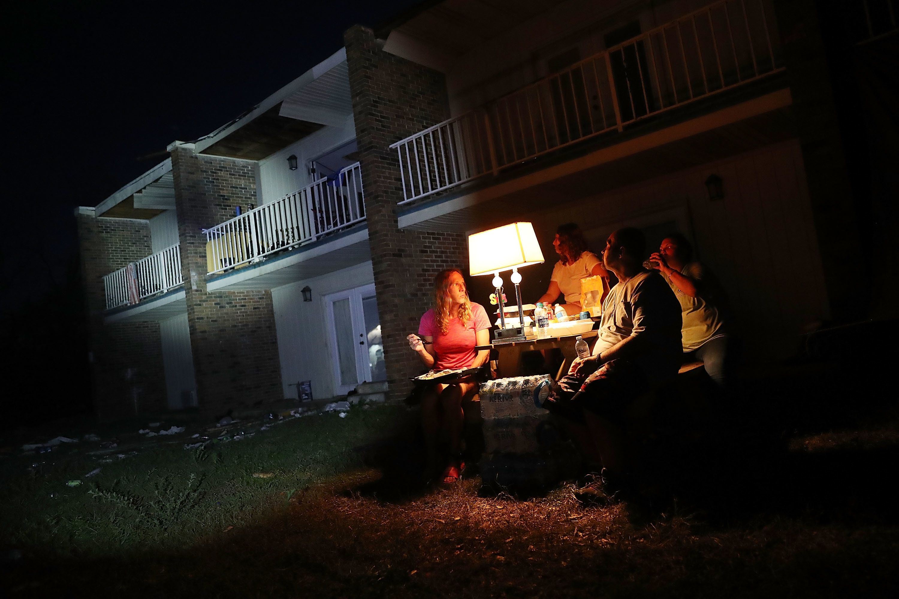 Danica Cherico and Shawn Gehlert use a generator to power a lamp outside their apartments, which lack electricity in Panama C