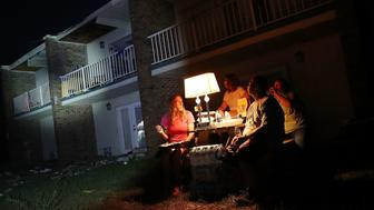 PANAMA CITY, FL - OCTOBER 15:  Danica Cherico and Shawn Gehlert use a generator to power a lamp as they sit outside their apartments that don't have electricty after it was damaged by Hurricane Michael on October 15, 2018 in Panama City, Florida. The death tolls stands at 18 blamed on Michael, which hit the Florida Panhandle as a Category 4 storm last week with sustained winds of 155 mph.   (Photo by Joe Raedle/Getty Images)