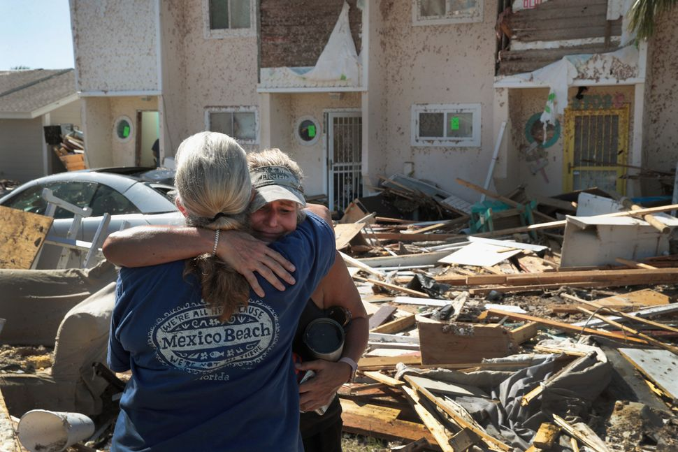 Neighbors Sherry Frantz (L) and Chris McNeal hug as they meet in front of their homes, which were destroyed by Hurricane Mich