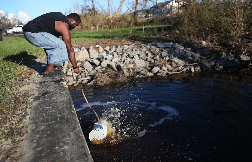 Kenston Robinson uses a bucket to get water from a canal to flush his family's toilet after much of the municipal infrastruct