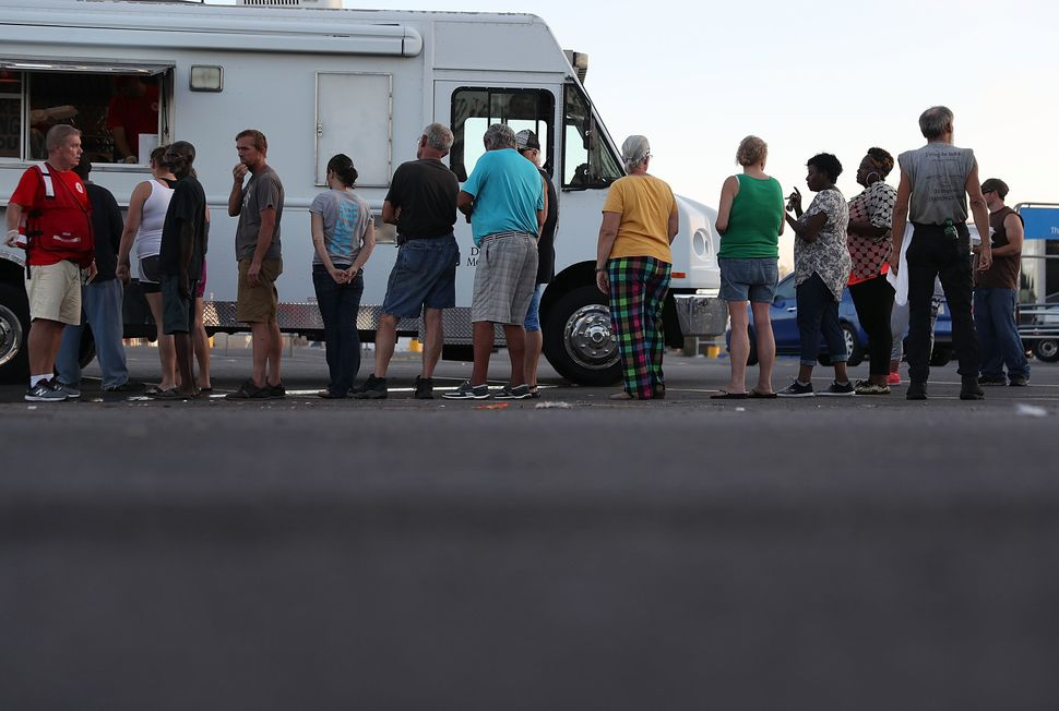 People stand in line to receive food from the Salvation Army emergency disaster services food distribution operation for peop