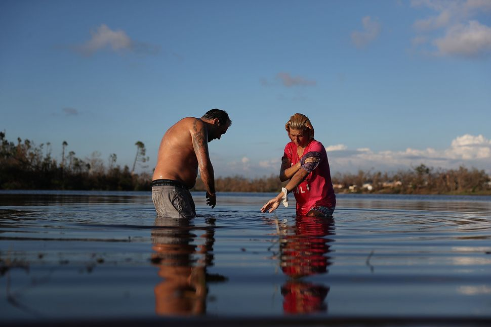 Justin Norman and Lisa Salle wash themselves in Lake Martin because their home has no running water in Panama City.