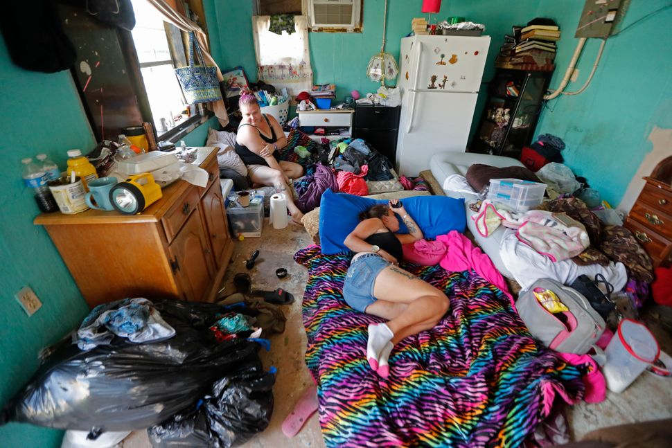 Amber Cousin sits by a window as Amy Lenain naps in a room they now share with multiple people at an evacuation shelter at Ru