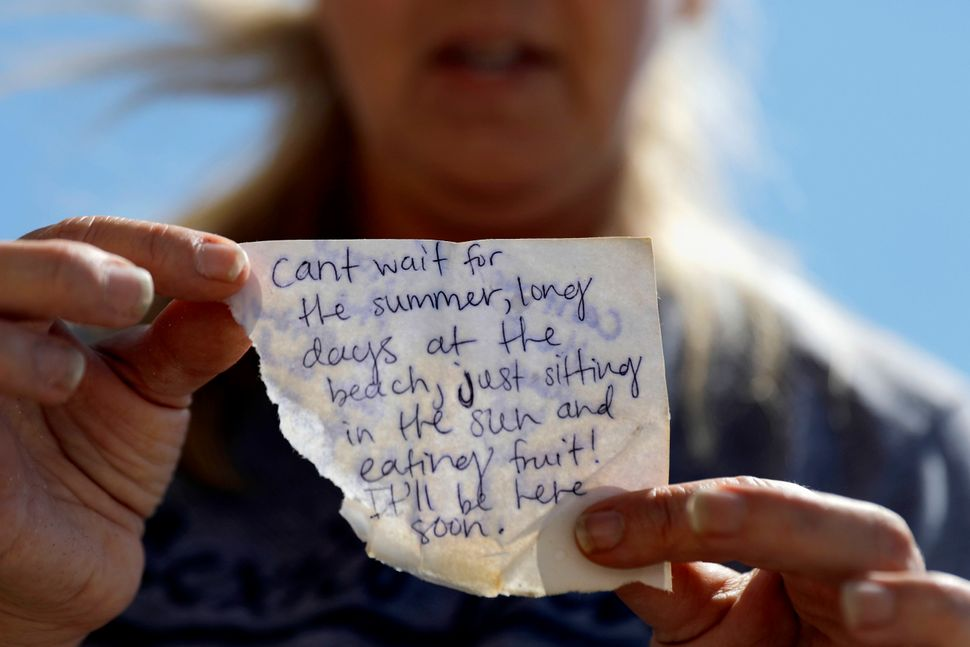 Candace Phillips holds a note she found in the rubble that her daughter left on a recent visit to their now-damaged home in M