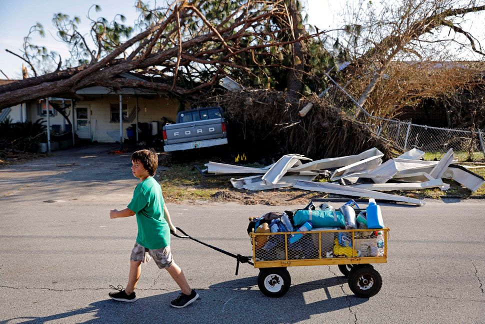 Anthony Weldon, 11, pulls a cart with his family's belongings as they relocate from their uninhabitable home to their landlor