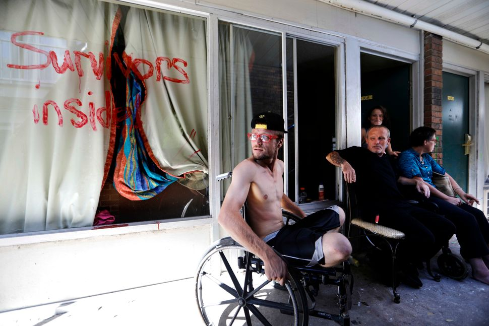 Wes Allen Jr., from left, sits with his father Wes Allen Sr., sister Alison, and mother Vicki outside their room at a damaged